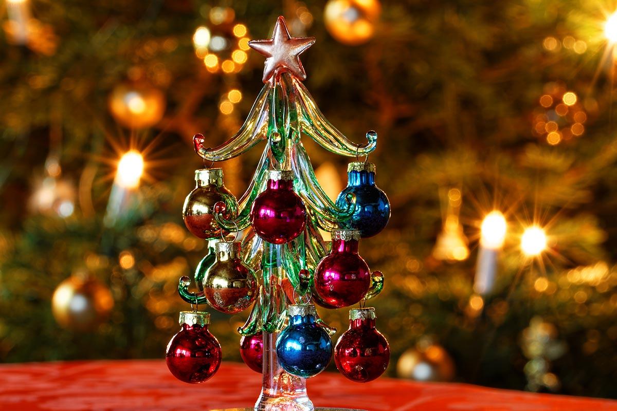 Deko-Weihnachtsbäumchen vor Weihnachtsbaum